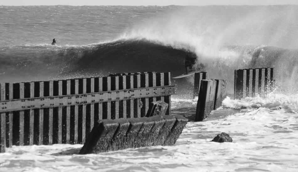 Winter surf here doesn\'t bode well for photographers. The light is weird... the water is a dirty chocolate brown.... But, the waves are pumping. The lack of green water sometimes requires black and white, but Florida charger Mark Dawson has relocated to the Outer Banks for the barrels, not the water color. Photo: Gallop