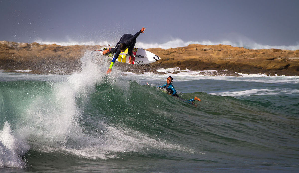"Kelvin Zemkhe putting on a show for the groms at the left in the bay. Photo: <a href=""https://www.facebook.com/pages/Pho-Tye-Studio/398591356893177?fref=nf\""> Tyerell Jordaan</a>"