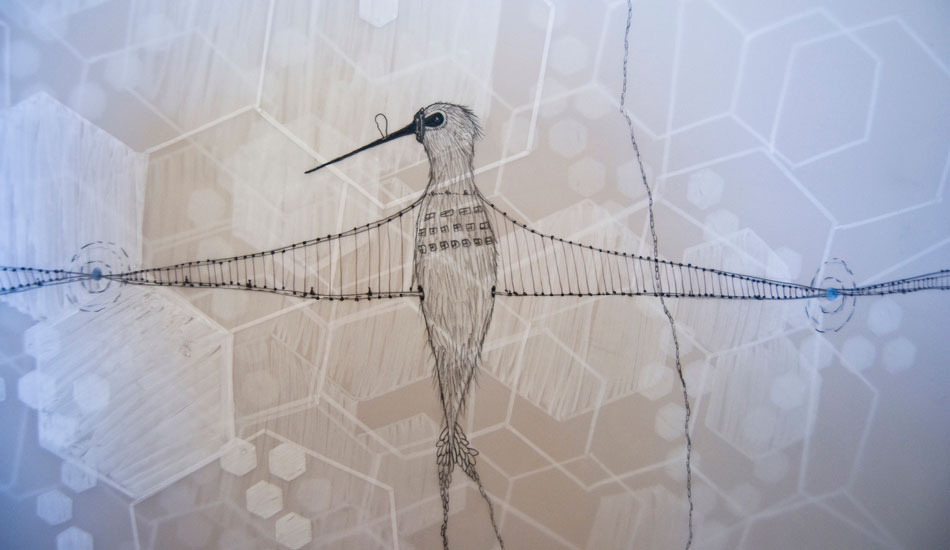 A hummingbird rests on layered Mylar and brown paper.