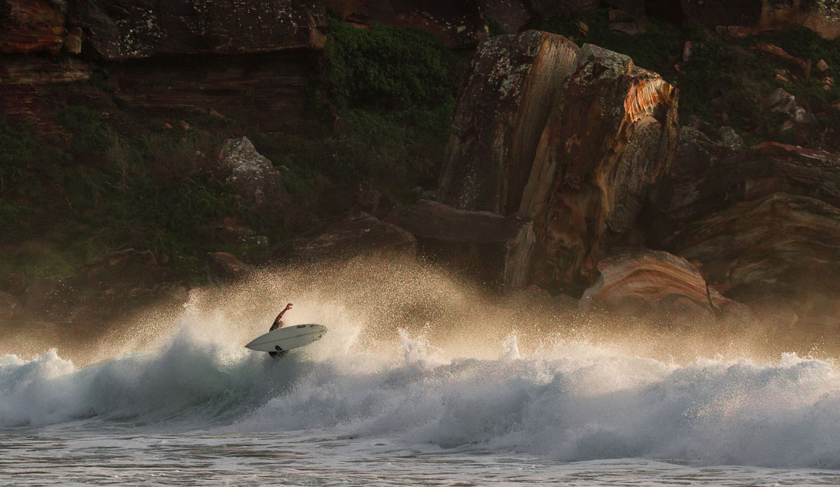 """This actually was quite a solid 6ft wave before the surfer ended his ride on the close-out. I like the rocks and the golden sunrise light shining in the spray in the background - gives the whole thing a nice sense of scale. Photo: <a href=\""""http://www.SurfLove.com.au/\""""> Chris Eyre-Walker.</a>"""