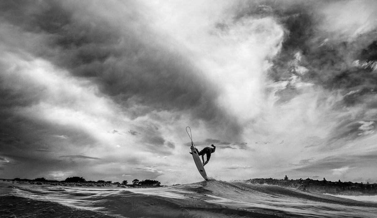 """A local surfer making the best of the conditions and pulling of a solid air. Most of the times people pick the shot where the surfer is highest up in the air. But in the row of shots I got here I picked the one just before he got back down. The dramatic sky and his position just touching the surface just came together nicely. Photo: <a href=\""""http://www.SurfLove.com.au/\""""> Chris Eyre-Walker.</a>"""
