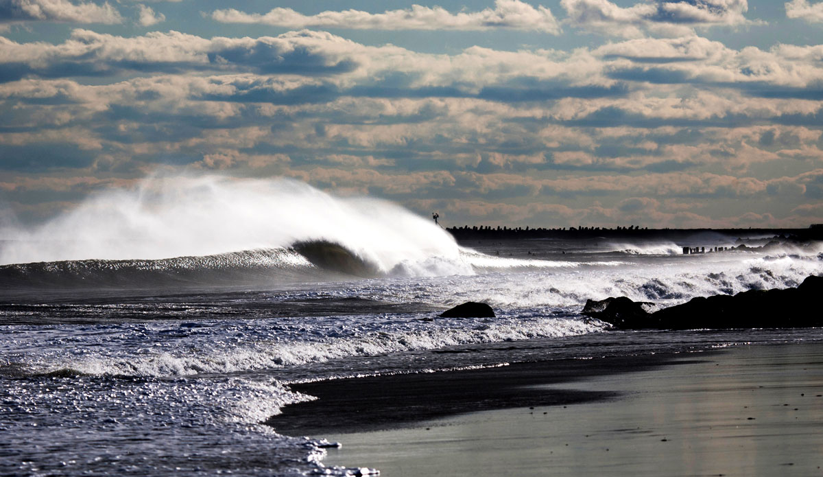 """Manasquan Inlet, NJ. \""""This photo is one of my favorite lineup photos I\'ve ever taken. I just love the big spray going over the back of the wave from the offshore winds and the glowing light effect in the shore break.\"""" Photo: <a href=\""""http://www.mikeincittiphotography.com/\""""> Mike Incitti.</a>"""