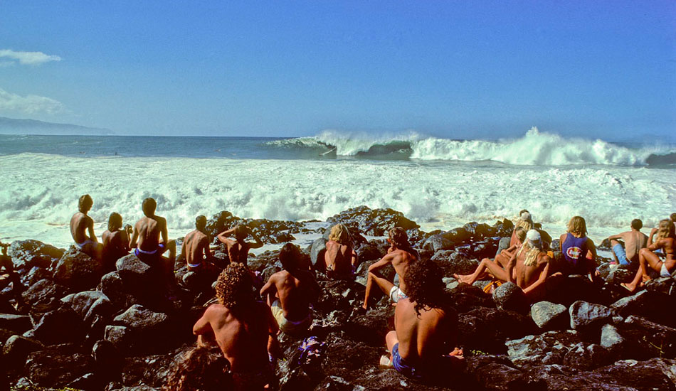 Thanksgiving Day, 1974: Five years after Greg Noll thundered into that giant wave at Makaha and then thundered off to NorCal to become a commercial fisherman, the first surf contest was held at Waimea Bay. The 1974 Smirnoff Pro has gone into legend as one of the best days of big-wave surfing in history. The minigun had changed big-wave surfing as much as it had evolved hotdog surfing, and the two Little Big Men who came out on top were as sleek and light as their surfboards.  If Reno Abellira were sitting on Jeff Hakman's shoulders, those two combined (Reno's 5 feet, 7 inches and 135 pounds + Jeff Hakman's 5 feet, 6 inches and 130 pounds) would have just barely surpassed the height or weight of a Greg Noll (6 feet, 2 inches and 230 pounds) or the Thunder Lizards who had dominated the big surf on their elephant guns through the previous decades.   At the end of an epic day of surfing, Reno Abellira beat Jeff Hakman by a fraction of a point. Photo: Jeff Divine
