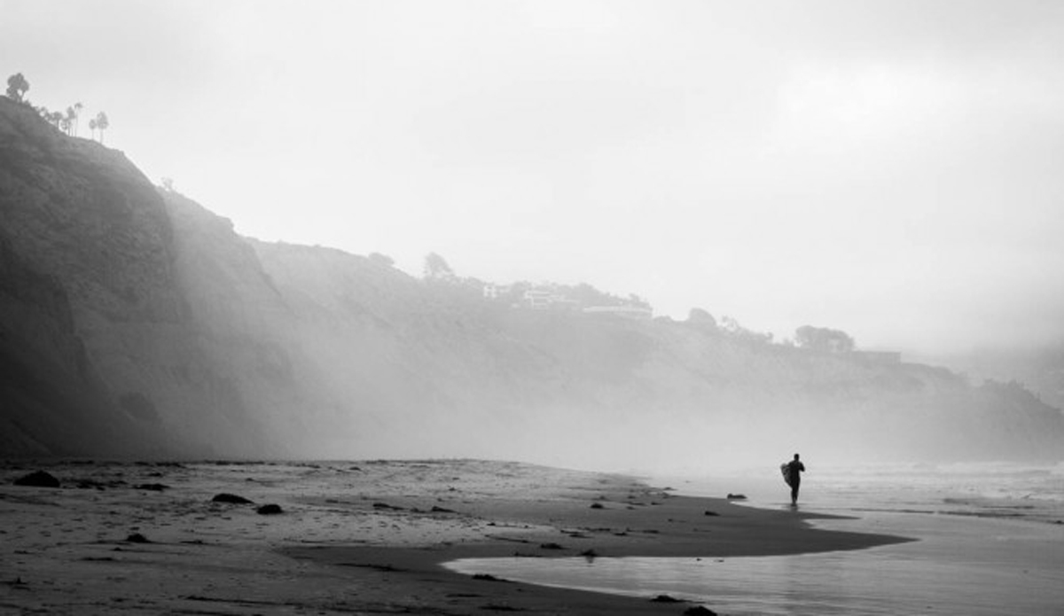 An unknown surfer making the morning walk to the beach front.