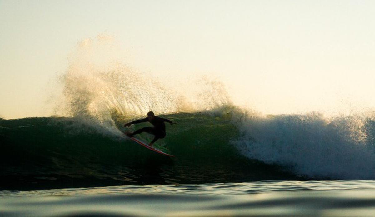 An unknown surfer spraying some golden water around.