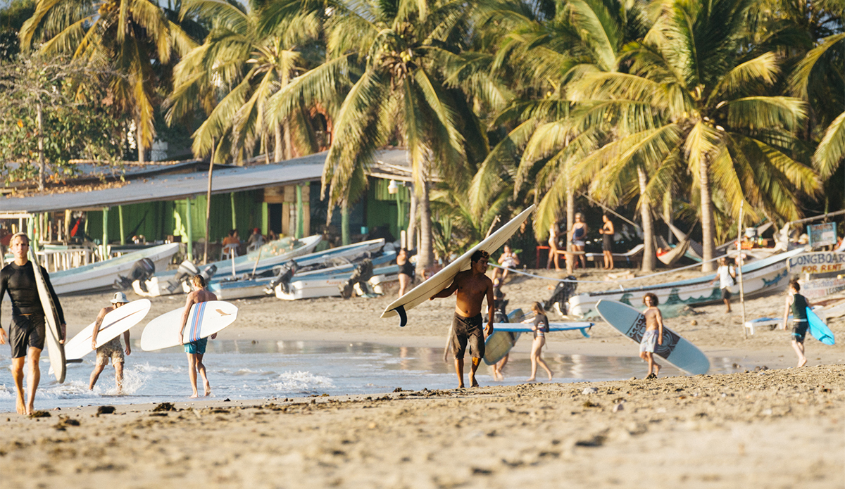 A typical scene of fishing boats, coconut laden palms, and surfers walking up the beach after long rides down the point. Photo Keoki Saguibo