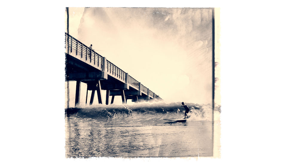 """This images is iconic because it depicts a local Mitch Kaufmann, (dubbed the mayor of Jax Beach, due to him knowing everyone, and having done a lot for our local surf community) aiming to shoot The Jacksonville Beach Pier on his 12 foot board. The pier has always been a wave magnet, and the waves here have produced a wealth of talent throughout the years. We have a very strong surf community here. Photo: <a href=\""""http://www.marksainwilson.com/?splash=1\"""" target=_blank>Mark Wilson</a>"""