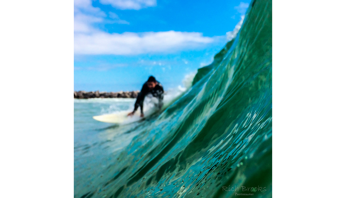 "Surfer turning away from the jetty at St. Andrew\'s State Park. Photo: <a href=""https://richbrooksphotography.squarespace.com/\"">Rich Brooks</a>"