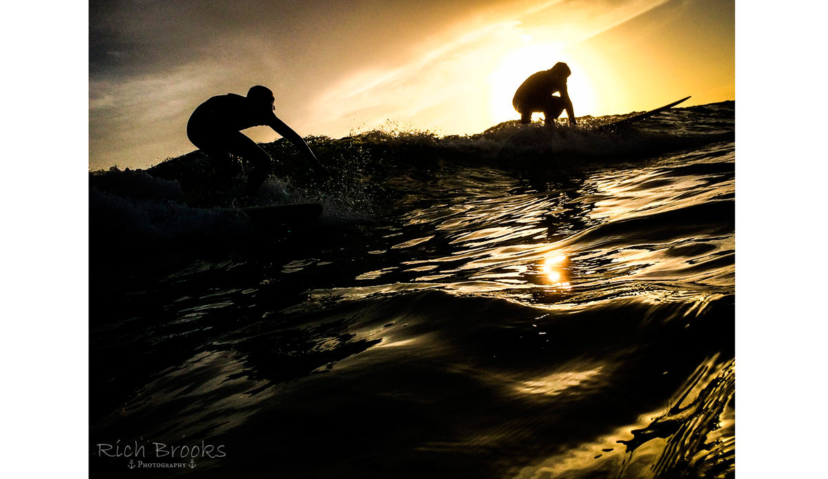 """Two surfers perfectly silhouetted against the sun. Photo: <a href=\""""https://richbrooksphotography.squarespace.com/\"""">Rich Brooks</a>"""