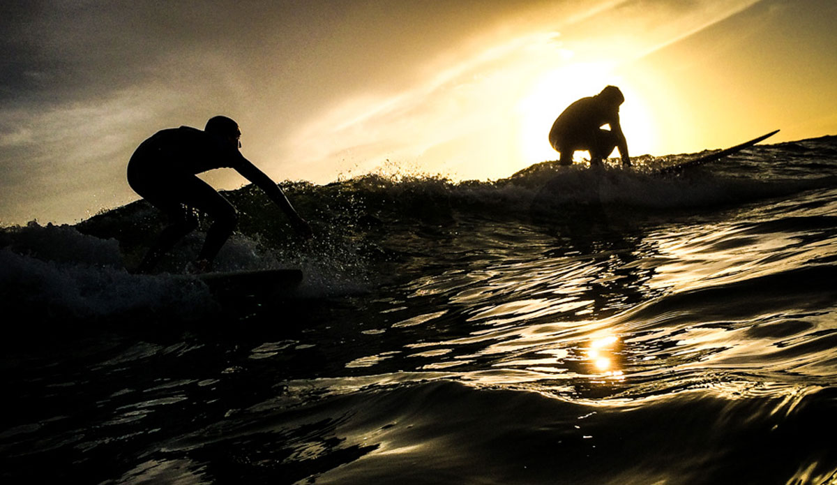"Two surfers drop in on a wave together, perfectly silhouetted against the setting sun. This time of day is called the golden hour for a reason. Photo: <a href=""https://richbrooksphotography.squarespace.com/\""> Rich Brooks</a>"