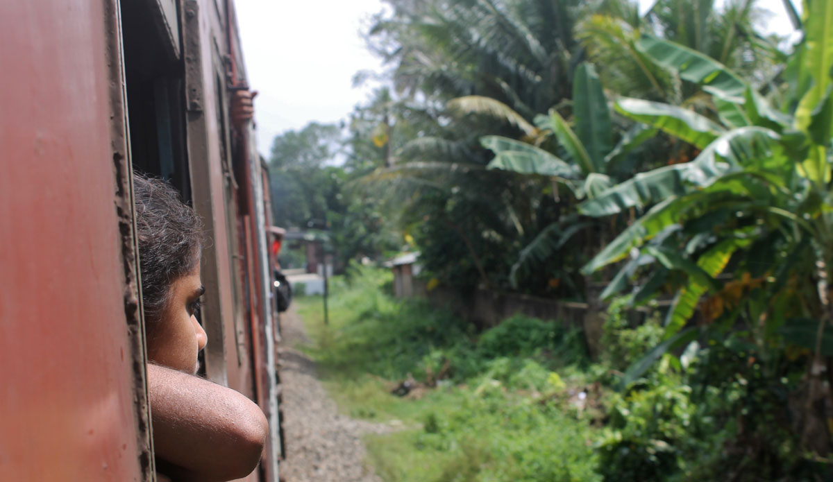 "A young girl enjoys the views from the train that takes you along the west coast of Sri Lanka. The trip is filled with views of rare wildlife, palm trees, and stunning beaches.  Photo: <a href=""http://www.ryanwattersphoto.com/\"">Ryan Watters</a>"
