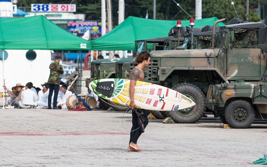 "Local surfer Dong-hoon Han heads out through army vehicles during the last typhoon season which brought great waves to the area. Photo: <a href=""http://www.shannonaston.com/\"" target=_blank>Shannon Aston</a>."
