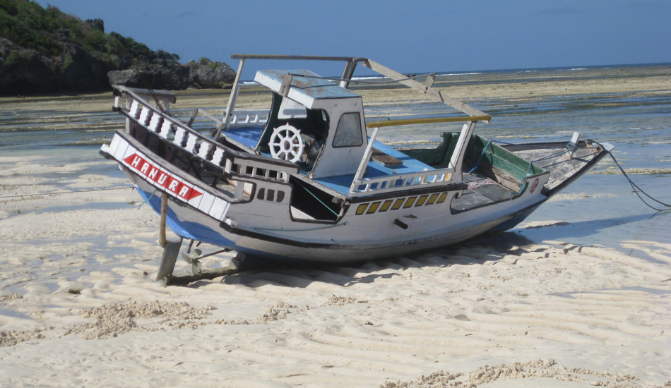 At low tide it becomes easy to walk the beach for miles and get around the small headlands.  This local boat is actually in excellent working condition. Image: Murphy