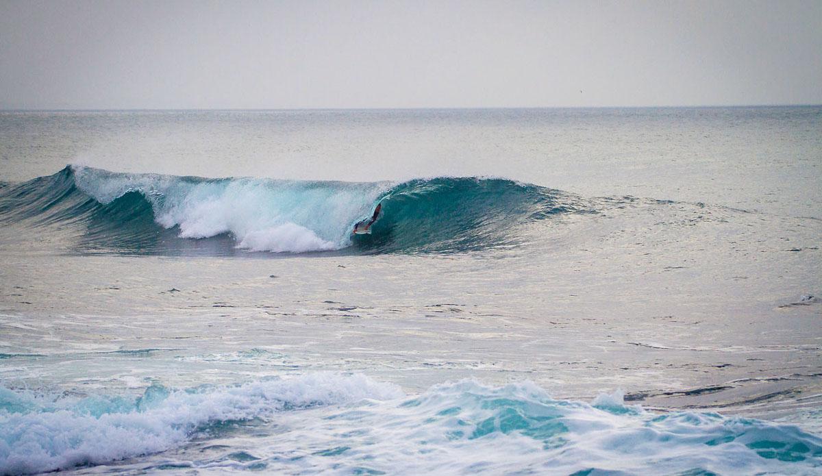 """Greg sneaks under a folding ocean.  Photo: <a href=\""""https://www.facebook.com/pages/Pho-Tye-Studio/398591356893177?fref=nf\""""> Tyerell Jordaan</a>"""