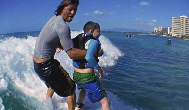 Kalani Robb teaches, through the Mauli Ola Foundation, a young boy afflicted by cystic fibrosis how to surf. Image: screenshot, Mauli Ola Foundation