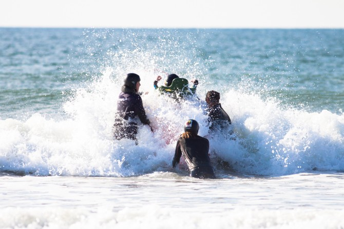 Getting the board through the waves takes teamwork