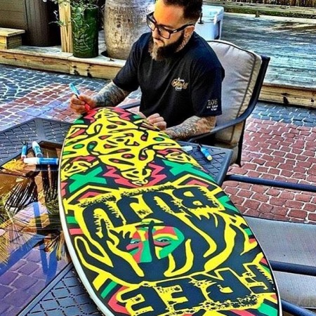 ark Longenecker puts finishing touches on the free-hand painted surfboard raffled off at Dub Massive 2016 benefiting Surfers For Autism.