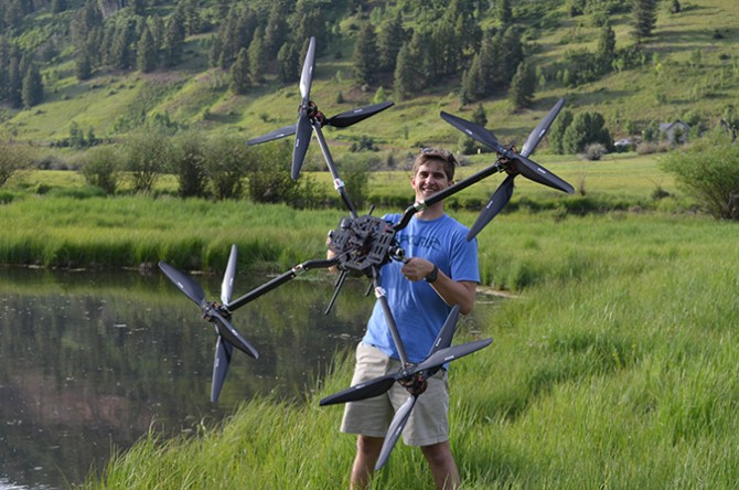 CTO Robert Blank with a drone designed for larger payloads.]