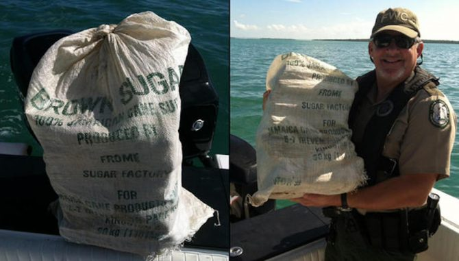 Florida Fish and Wildlife Commission officer, Bobby Dube, poses with a bag of floating marijuana found floating just offshore of the Keys. Photo: FWC