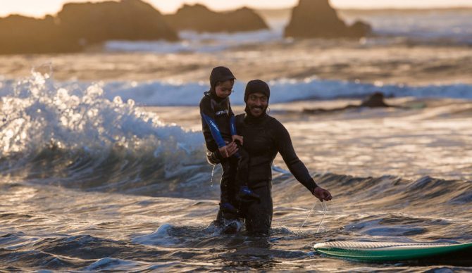 Ramón teaching his son, Inti, to surf at his beloved surf spot, Punta De Lobos. Chile. Photo: Jeff Johnson