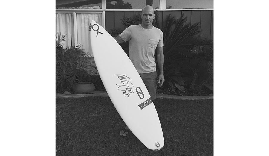 Kelly Slater touched a pen to surfboard and made it worth $25,000. Photo: SurfAid
