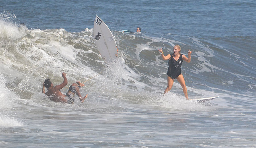 Woman surfer dropping in on wave.
