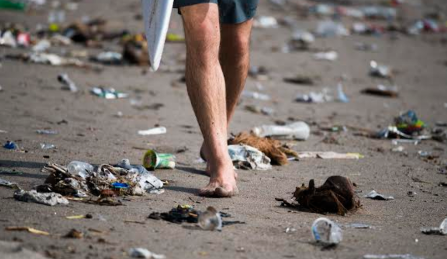 Trash in Bali as surfer walks beach.