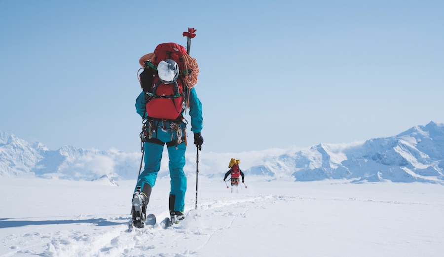 Jess Roskelley (blue) and David Lama (black) ski back to base camp after a recon of the 13,000' southeast face of Mount Logan. Yukon, Canada.