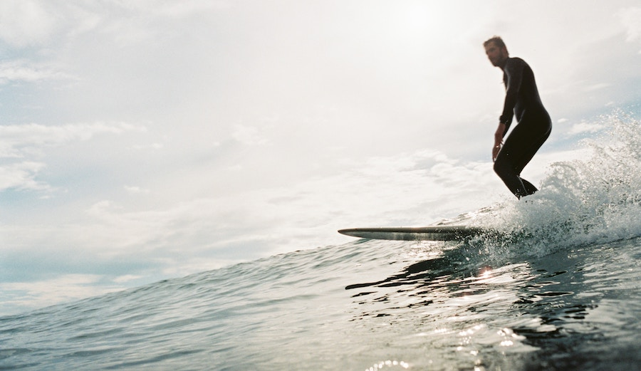 A surfer skims along on a longboard.