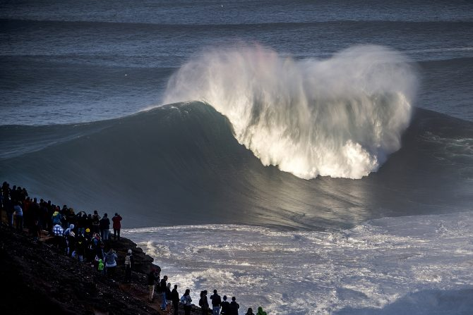 A big wave in Nazare, Portugal with crowds.