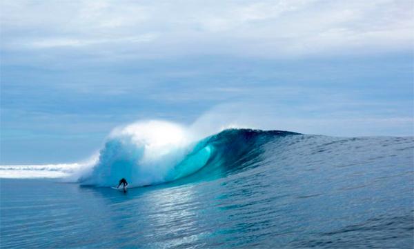 A surfer rides Cloudbreak in Fiji