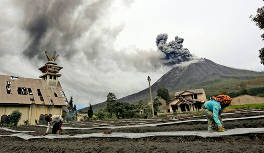 Villagers work at their farm as Mount Sinabung spews volcanic materials during an eruption, in Karo, North Sumatra, Indonesia