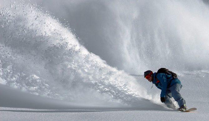 a snowboarder rides powder
