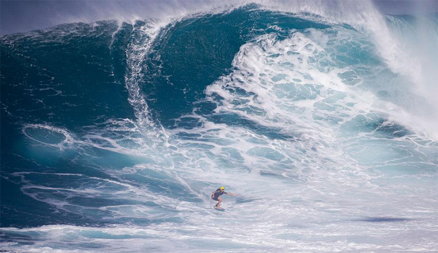 Sean McClenahan riding massive Jaws on a skimboard.