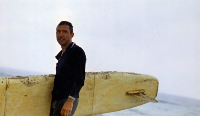 Russian surfer Nikolai Petrovich Popov holding a surfboard