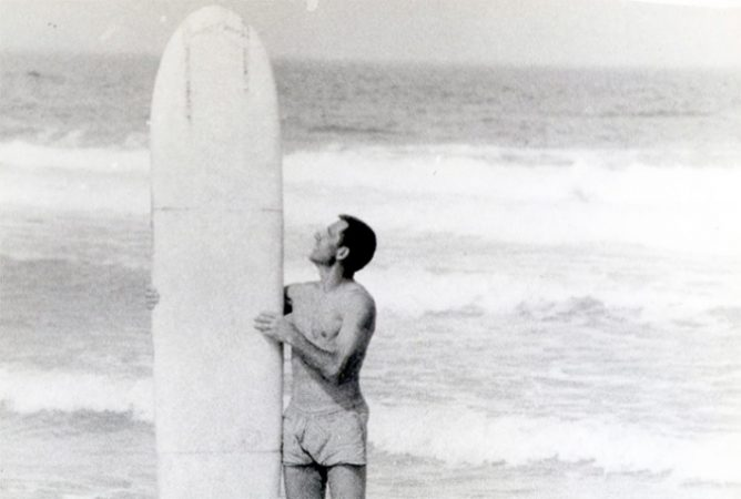 Nikolai Petrovich Popov with his surfboard in front of the ocean