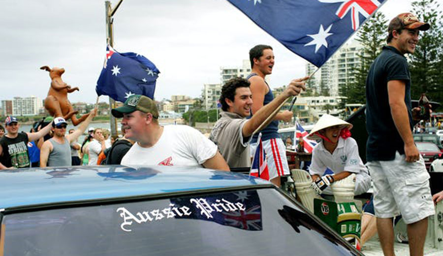 Youths wave Australian flags to passersby at Cronulla Beach in Sydney