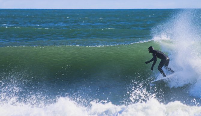 a man winter surfs in a full wetsuit
