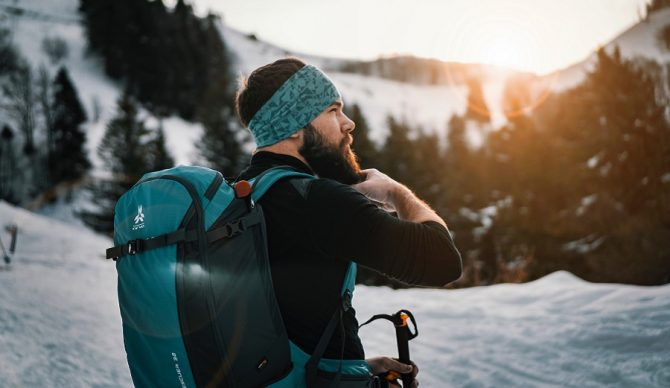 skier on mountain with backpack from unsplash