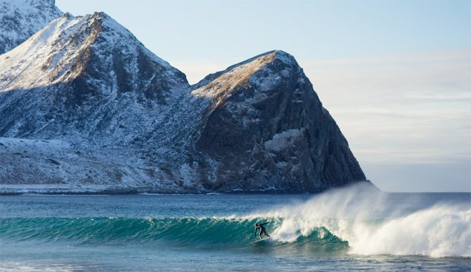 a surfer catches a wave with a snowy mountain behind