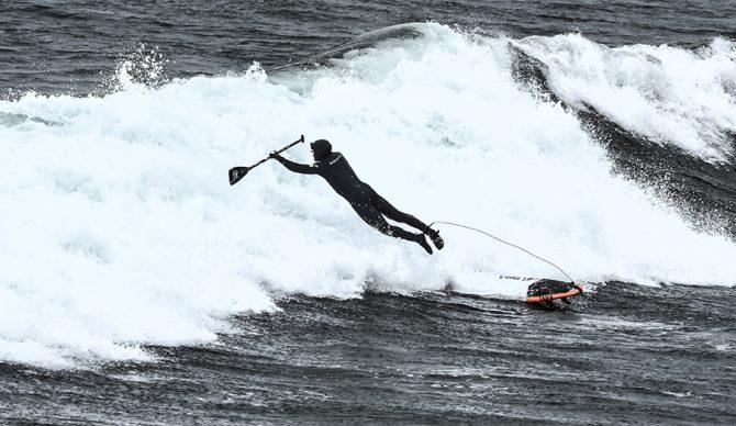 A Sup Surfer bails off a wave