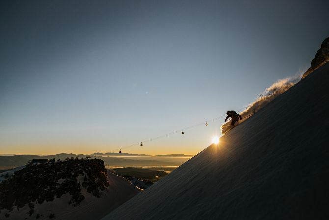 ski patroller skiing in front of the sunrise
