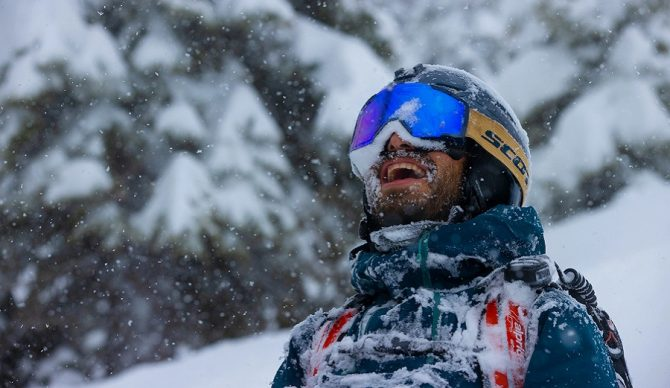 stoked dude in the snow with snow on his face skiing
