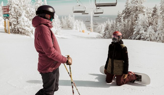 skier and snowboarder under the lift on a powder day