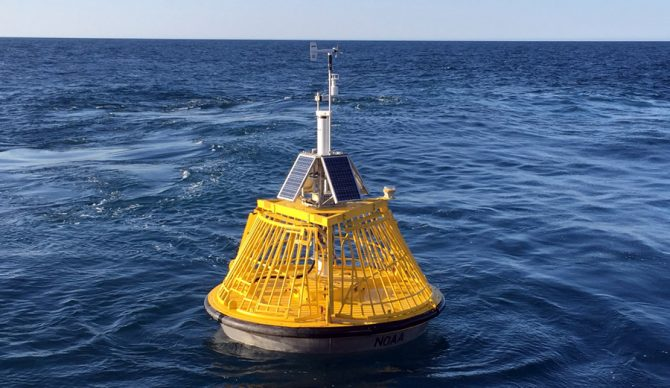 A buoy that gives wave height and wind informations sits in the ocean