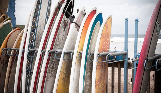 Composite surfboards sit in a rental rack