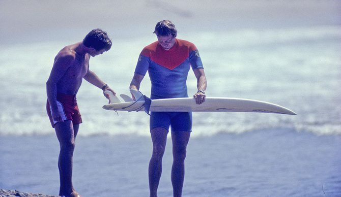 Simon Anderson holds a surfboard with a thruster setup