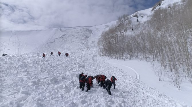 Rescue teams on a snowy slope work to excavate a lost person.