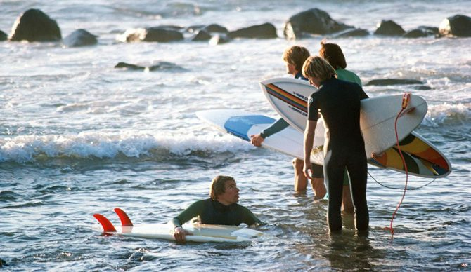 surfers with surfboards getting in the water