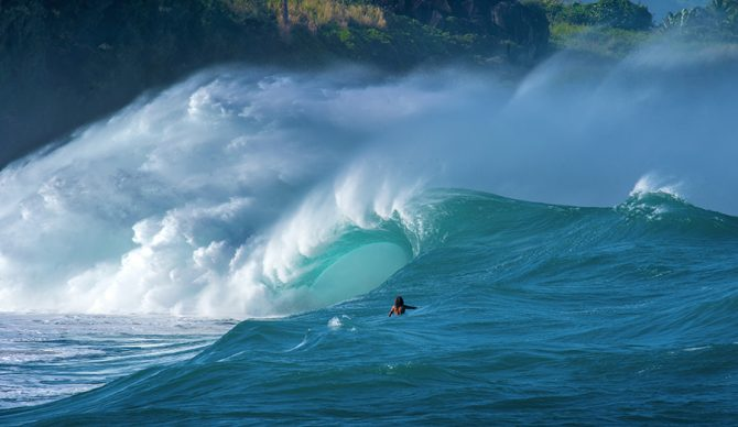A surfer looks at a giant wave